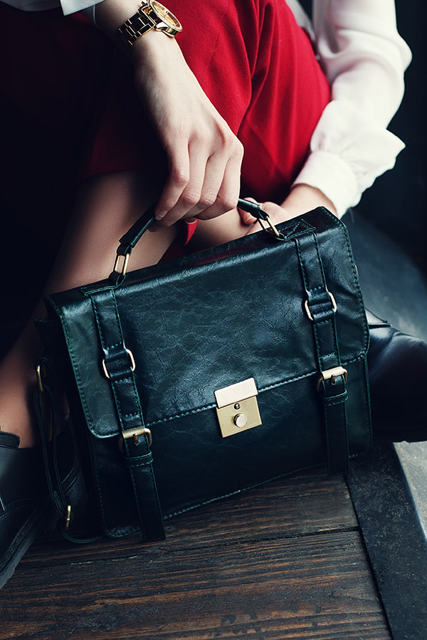 Close up of woman sitting down with a black leather briefcase at her feet.